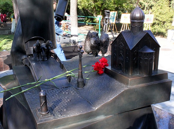 Установленные на бронзовом столике статуэтки являются символами благ цивилизации, которые оставил Ростову городской глава. Это уличная колонка, мост, мощеные дороги и тротуары, конка, уличный фонарь, деревья и храм, построенный Байковым на собственные средства.
