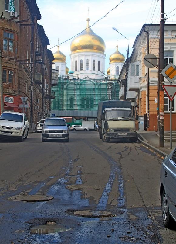 Общий архитектурный облик: черная лужа с грязью на фоне белого фасада храма.